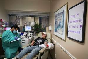 "Alfredo Gutierrez, left, fills out paperwork as Conner Scott donates plasma at Houston Methodist Hospital on Friday, May 15, 2020 in Houston. Scott, a sophomore at Texas A&M University, has donated his plasma for a Houston Methodist study seven times since recovering from COVID-19 in late March. He researched plasma treatments himself before deciding to contribute. ""It's pretty selfish if I have something that could help people and I'm not doing anything about it,"" he said."