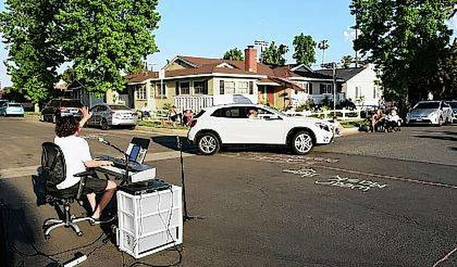 Musician Adam Chester (left) waves to a neighbor driving by May 9 as he performs his weekly neighborhood concert in the Sherman Oaks section of Los Angeles. Normally, Chester is a surrogate Elton John, singing and playing the rock superstar's parts at rehearsals with his band. With that work on hold, Chester has been giving concerts to his neighbors from a safe social distance in front of his house. Photo: Chris Pizzello | Associated Press