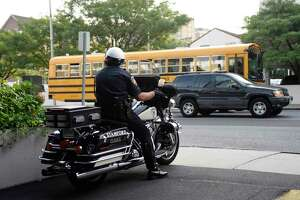 Stamford Police Officer Jeffrey Booth sits along Summer Street on the lookout for drivers illegally passing school buses on the first day of the 2015 school year in Stamford, Conn. Monday, Aug. 31, 2015.