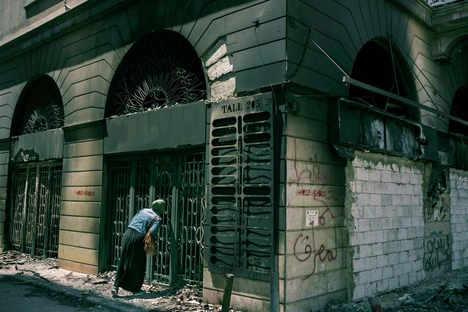 A woman looks inside a building in early May after it was torched during clashes in Tripoli, Lebanon, as the devaluation of the Lebanese currency triggered a new wave of protests. Photo: Photo For The Washington Post By Lorenzo Tugnoli / Lorenzo Tugnoli