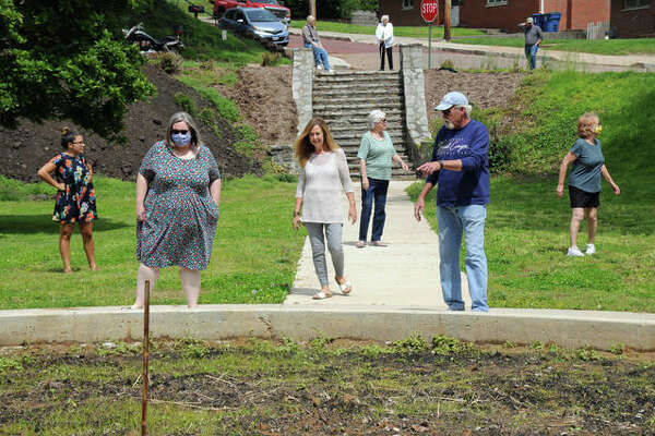 Area residents working on the Cousley Sunken Garden in Alton discuss the plantings that will be located in the garden's center. The garden in a lesser known part of Riverview Park is being transformed by neighborhood volunteers who are carrying on the passion and dedication of the garden's namesake, the late Mary Lou Cousley.