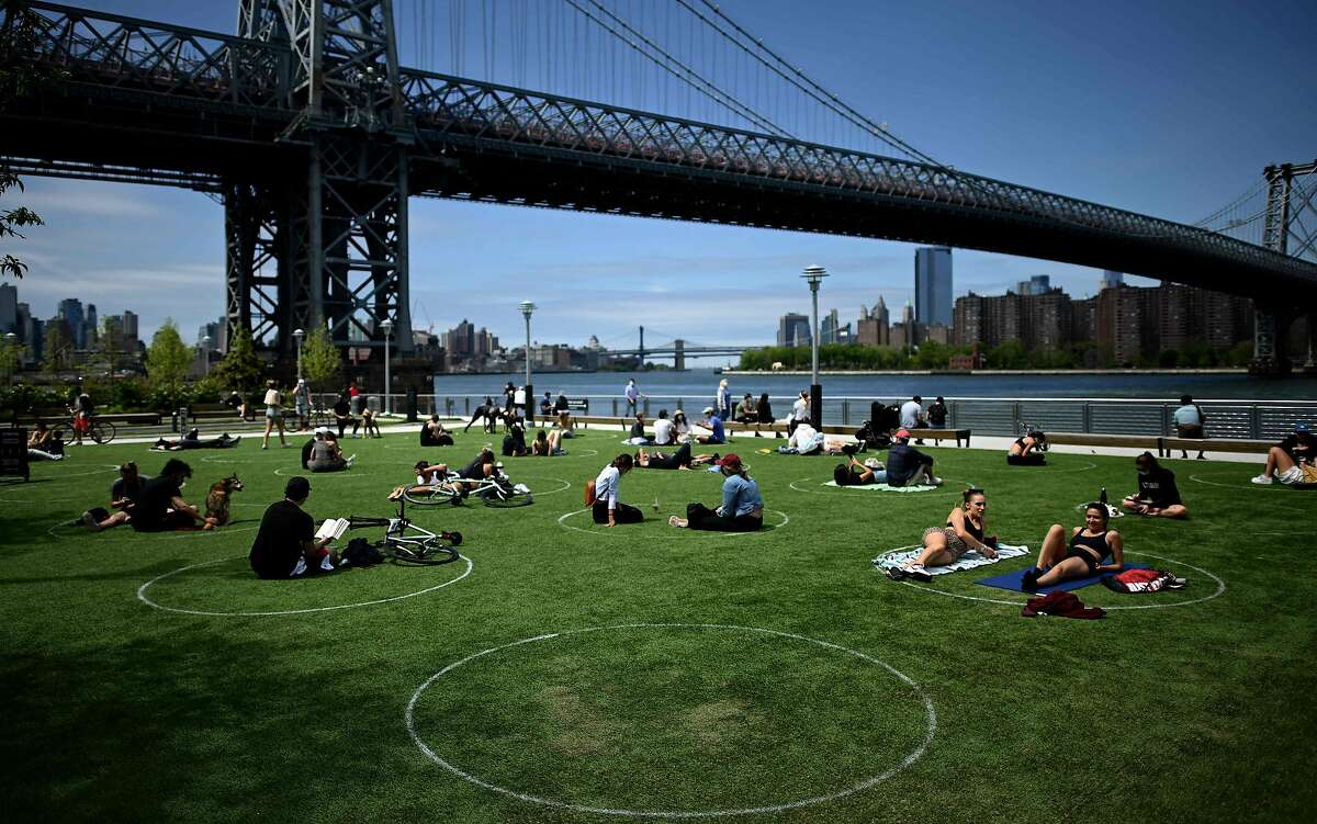 People are seen practising social distancing in white circles in Domino Park, during the Covid-19 pandemic on May 17, 2020 the in Brooklyn borough of New York City. (Photo by Johannes EISELE / AFP) (Photo by JOHANNES EISELE/AFP via Getty Images)