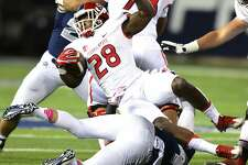 """FILE - In this May. 17, 2020, file photo, Fresno State's Dontel James is tackled by Utah State's Chase Christiansen during an NCAA college football game in Logan, Utah. San Diego State is looking at having football players return to campus no earlier than July 7 and is making plans to play the season as scheduled, athletic director J.D. Wicker said. SDSU is proceeding because it envisions a fall schedule that includes a hybrid model of classes, in which some students will be on campus for in-person instruction such as labs, while other classes will be online. NCAA President Mark Emmert said recently that campuses must be open """"in one fashion or another"""" in order to have sports this fall. (John Zsiray/Herald Journal via AP)"""