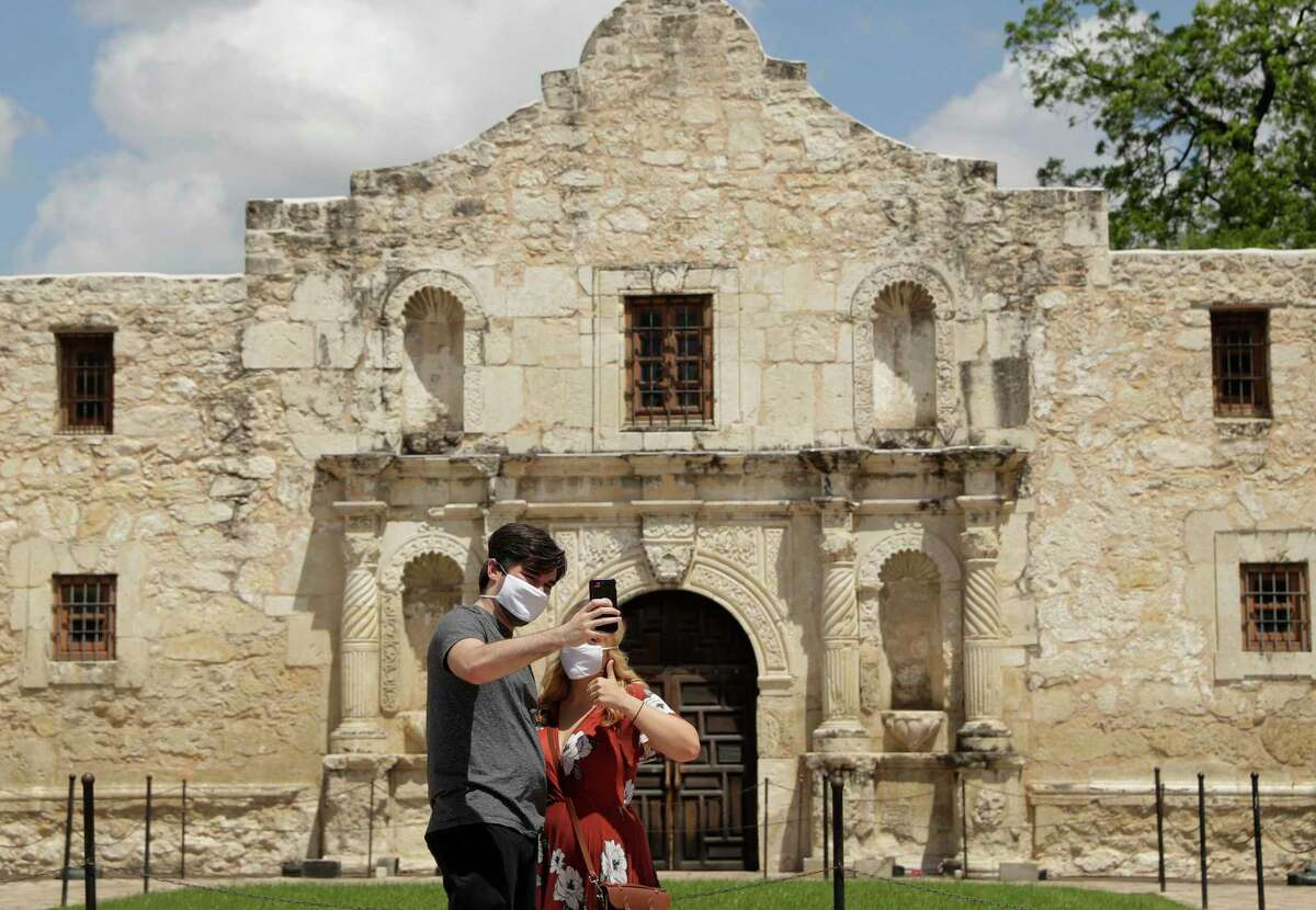 A couple wearing face mask for protection from the coronavirus take a selfie at the Alamo in San Antonio, Wednesday, May 13, 2020. The Alamo remains closed to visitors due to the COVID-19 pandemic. Mayor Ron Nirenberg and County Judge Nelson Wolff are urging San Antonio area residents to continue wearing masks and maintaining a 6-foot social distance from others when out in public to prevent a resurgence of the deadly novel coronavirus.