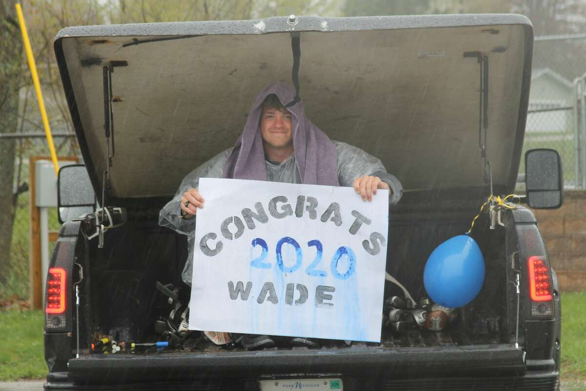 """OnekamaHigh School graduates sat in the back of their cars, on top of their cars or stood next to them during a parade in their honor on Sunday evening in the school parking lot following their """"virtual graduation."""