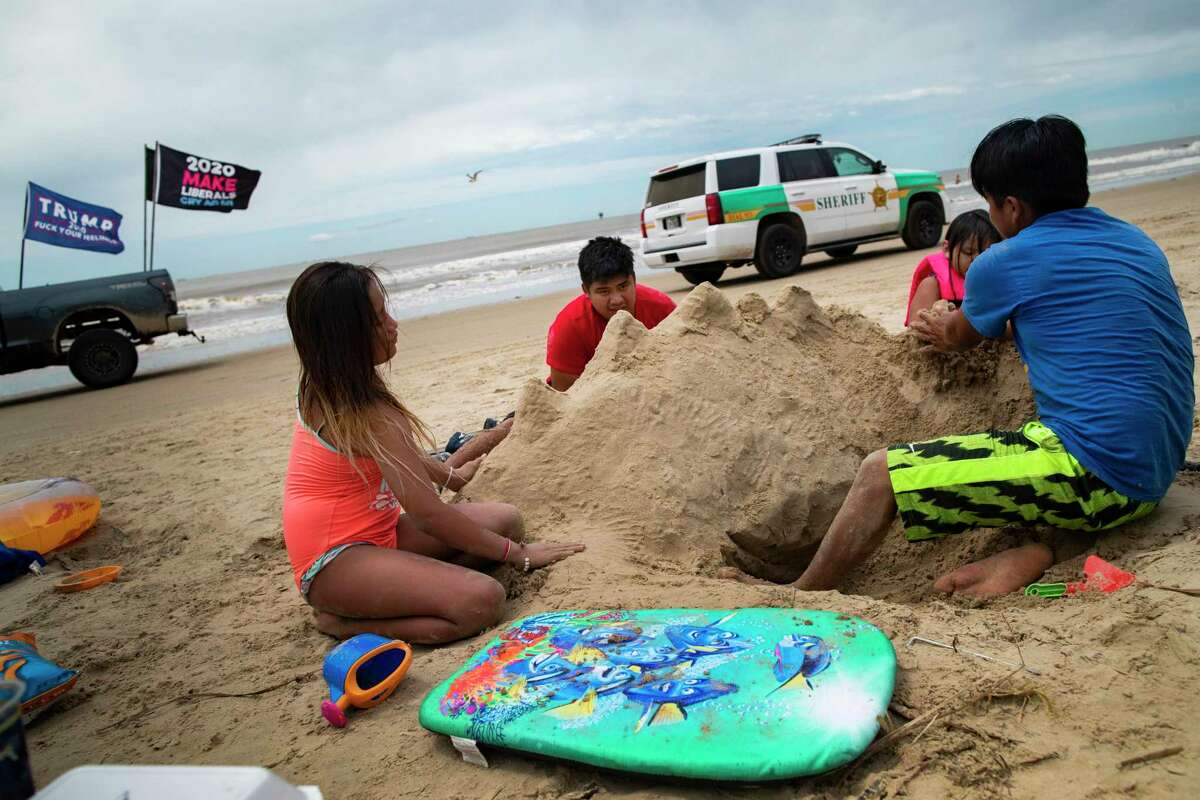 The Puac family of the Beaumont area, build a sand structure during their visit to the Crystal Beach, Sunday, May 17, 2020. In the background a vehicle with a Trump campaign flag drives by.