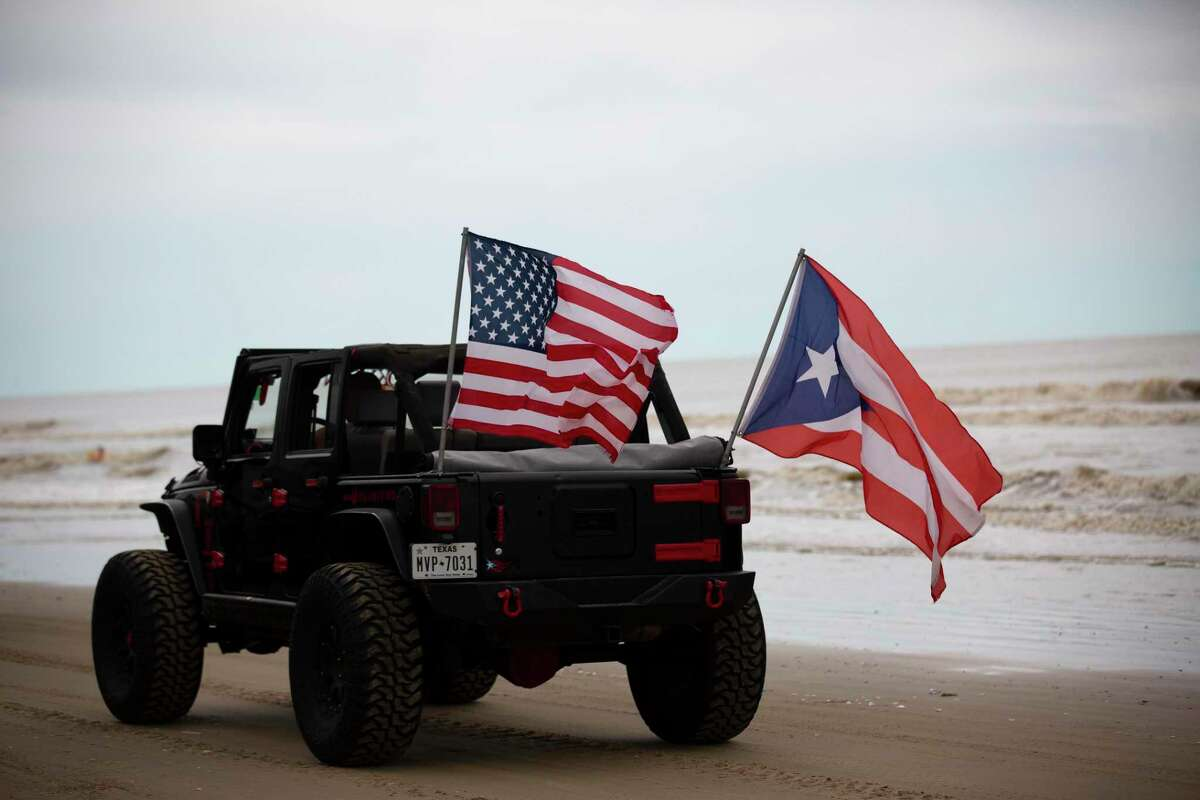 A Jeep drives by with both the United States flag and the flag from the island of Puerto Rico, which is a territory of the United States, Sunday, May 17, 2020 in Crystal Beach. Many beach goers arrived to the beach with different flags proudly installed on their vehicles showcasing their identities and delivering different messages.