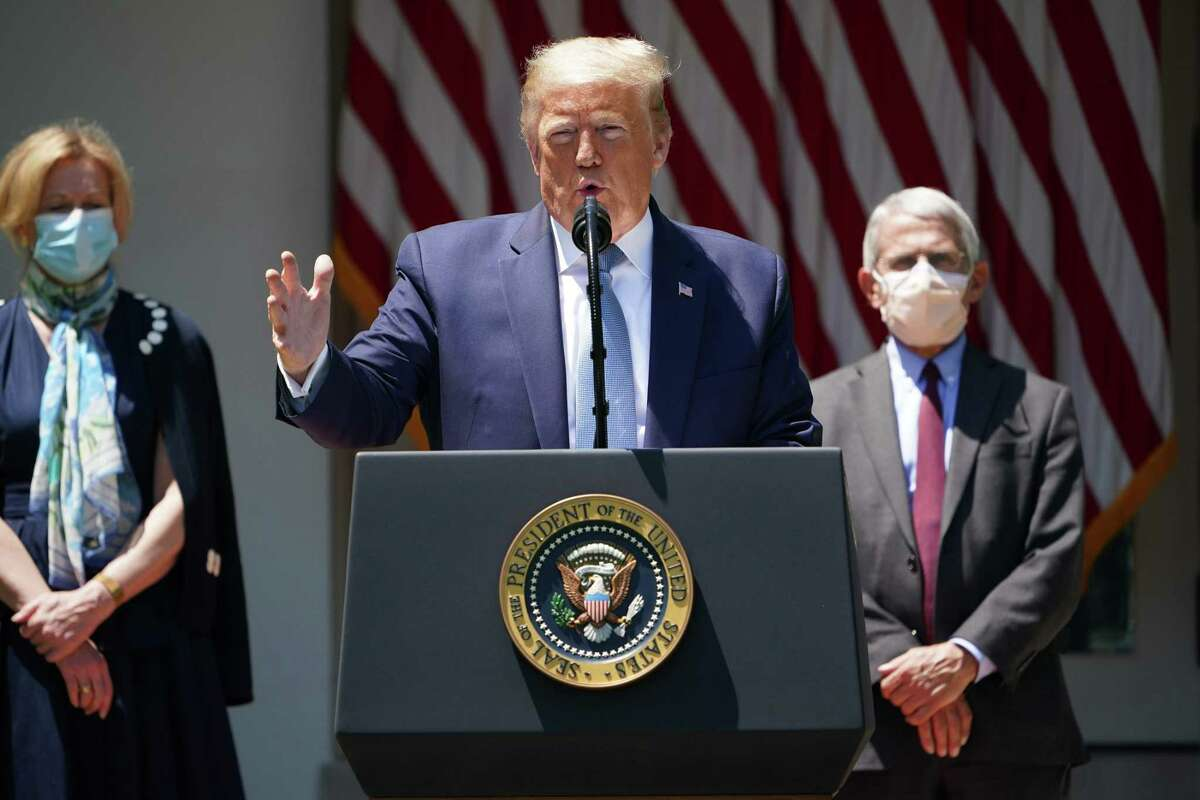 FILE. President Donald Trump with Deborah Birx, left, the response coordinator for the White House Coronavirus Task Force, and Dr. Anthony Fauci, Director of the National Institute of Allergy and Infectious Diseases, speaks on vaccine development. (Photo by MANDEL NGAN/AFP via Getty Images)