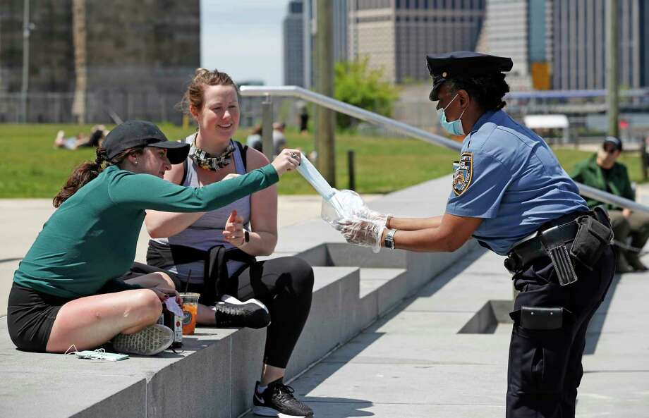 New York Police Department School Safety officer Bynoe, right, hands out face masks to women at Brooklyn Bridge Park during the coronavirus pandemic, Sunday, May 17, 2020, in New York. (AP Photo/Kathy Willens) Photo: Kathy Willens / Copyright 2020 The Associated Press. All rights reserved.