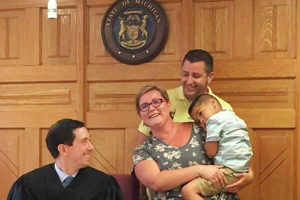 In this file photo, Probate Court Judge Tyler Thompson assists the Dermyer family with their adoption. Thompson said his favorite part of serving as a judge in Mecosta and Osceola counties is helping with adoption cases.