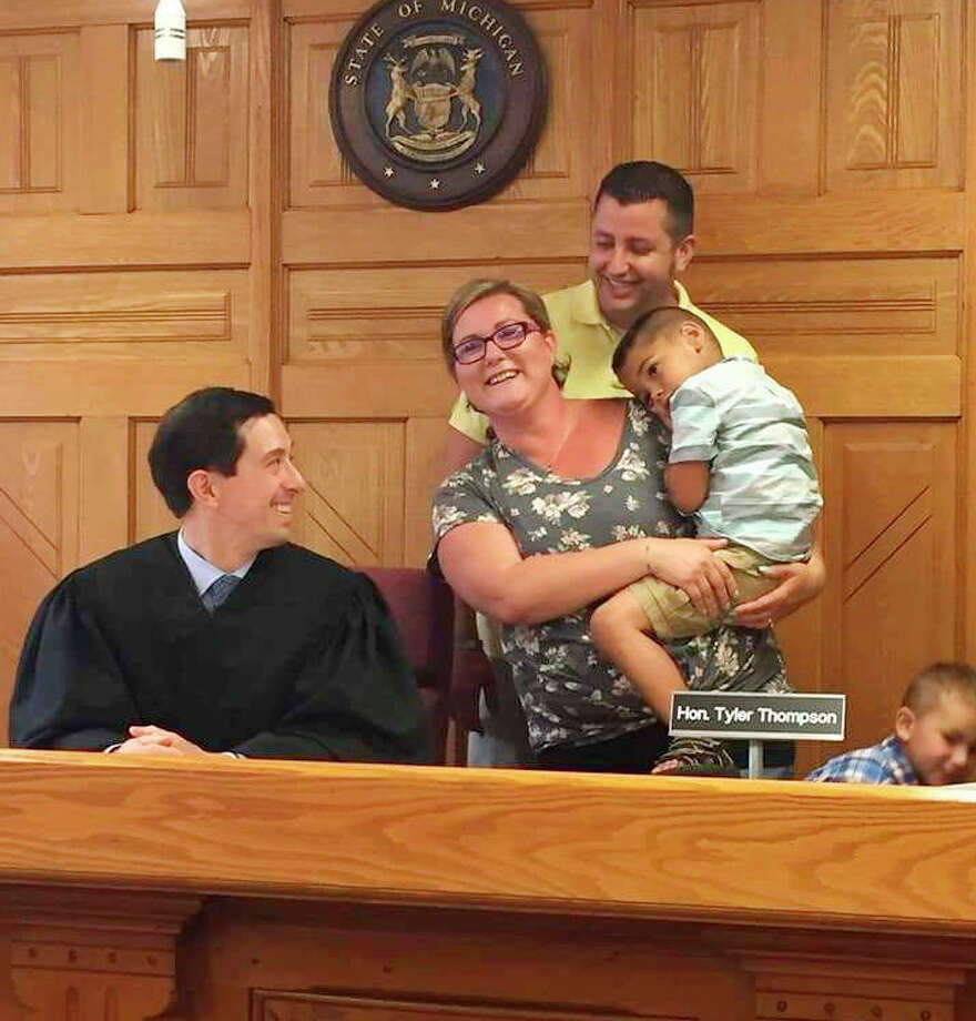 In this file photo, Probate Court Judge Tyler Thompson assists the Dermyer family with their adoption. Thompson said his favorite part of serving as a judge in Mecosta and Osceola counties is helping with adoption cases. Photo: Courtesy Photo