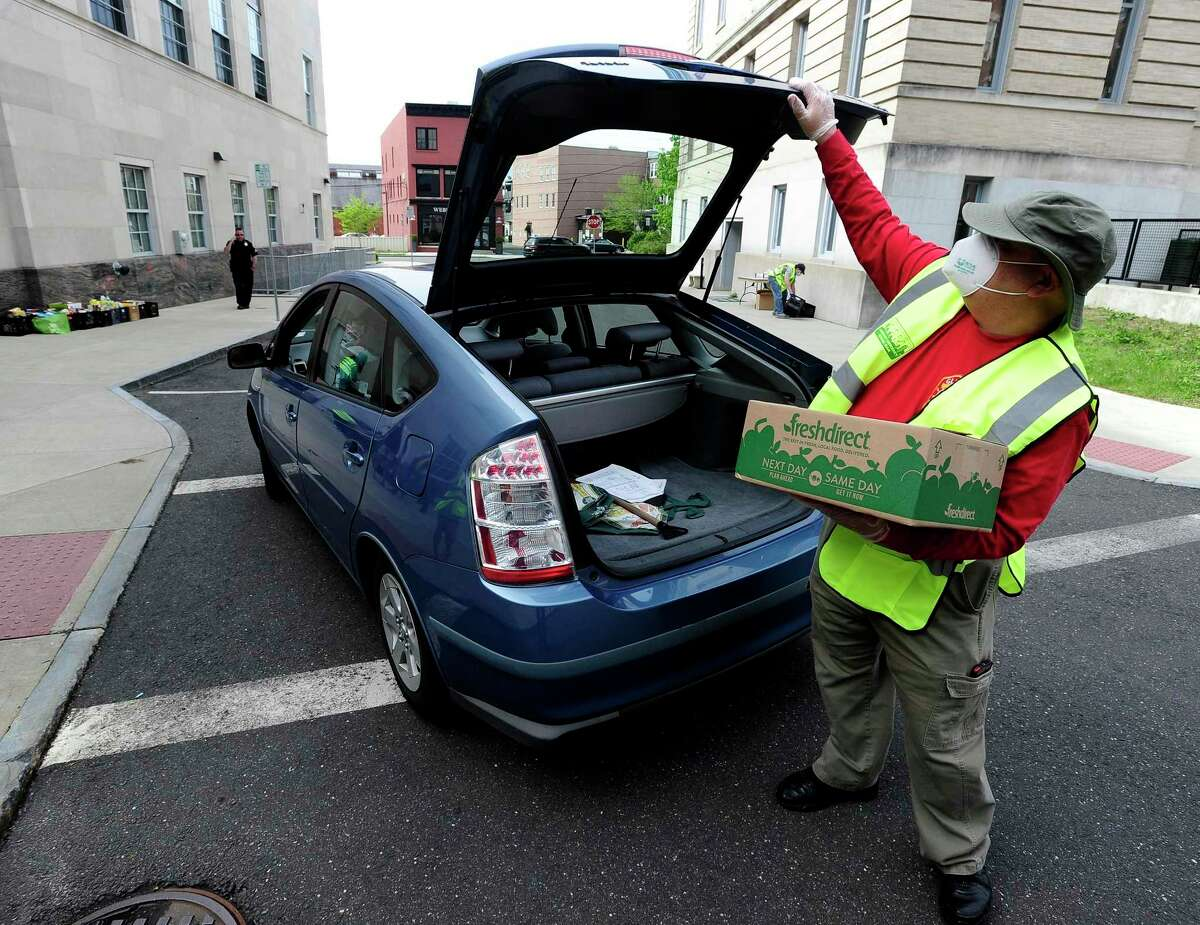 John Mastracchio collects a donation from a resident as the Greenwich Police Department, partnering with Neighbor to Neighbor, conduct a Community Food Drive on Saturday, May 16, 2020 in Greenwich, Connecticut. A volunteer group, half a dozen members of the Community Emergency Response Team (CERT) assisted police officers in collecting over seven truckloads of non-perishable food items donated by residents. In exchange for non-perishable items, face masks were given as a thank you for helping out those in need.