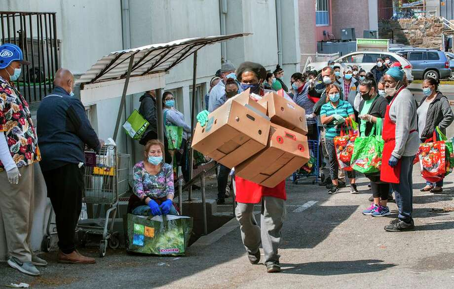Daniel White, of the 164 Wilson Food Pantry, carries out empty boxes as people wait outside for their numbers to be called. Photo: Conn. Health I-Team
