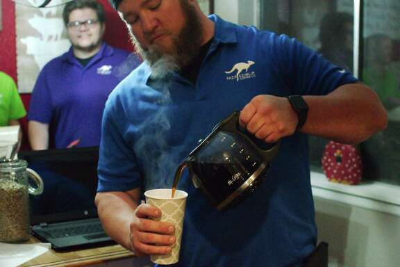 Fair Dinkum Coffee Co. President Chris Clark pours a cup of brewed coffee. The novel coronavirus pandemic has dramatically affected the online business, which has seen sales drop and access to raw materials slowed.