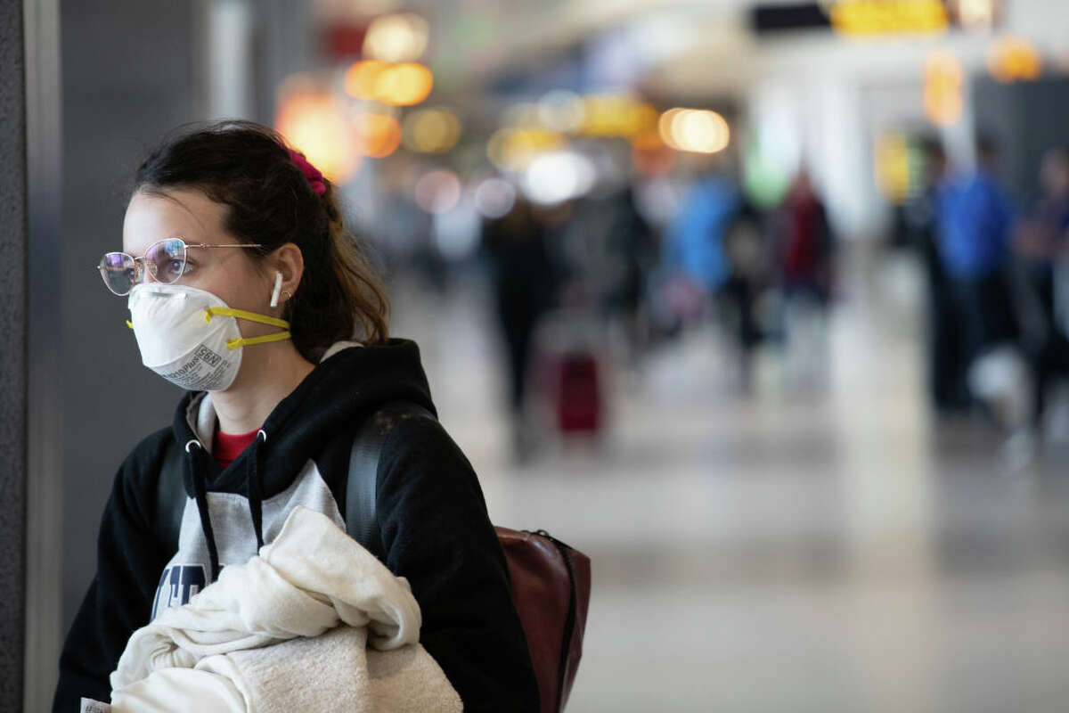 SEATTLE, WA - MARCH 15: A passenger wearing a mask prepares to board a flight departing the Seattle-Tacoma International Airport on March 15, 2020 in Seattle, Washington. The state of Washington has over 600 confirmed cases of coronavirus (COVID-19) and U.S. airports have been crushed with returning citizens after restrictions on travel from Europe were implemented. (Photo by John Moore/Getty Images)