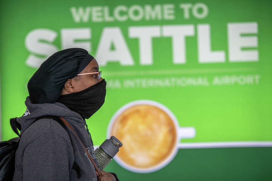 SEATTLE, WA - MARCH 15: A passenger wearing a mask walks through the Seattle-Tacoma International Airport on March 15, 2020 in Seattle, Washington. The state of Washington has over 600 confirmed cases of coronavirus (COVID-19) and U.S. airports have been crushed with returning citizens after restrictions on travel from Europe were implemented. (Photo by John Moore/Getty Images) Photo: John Moore/Getty Images / 2020 Getty Images
