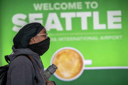 SEATTLE, WA - MARCH 15: A passenger wearing a mask walks through the Seattle-Tacoma International Airport on March 15, 2020 in Seattle, Washington. The state of Washington has over 600 confirmed cases of coronavirus (COVID-19) and U.S. airports have been crushed with returning citizens after restrictions on travel from Europe were implemented. (Photo by John Moore/Getty Images)