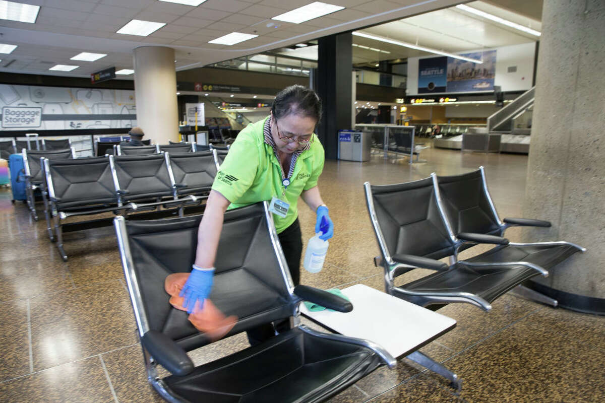 SEATTLE, WA - MARCH 08: Vui Truong, from Burien, WA cleans a seating area Seattle-Tacoma International Airport (also known as Sea-Tac Airport) on March 8, 2020 in Seattle, Washington. The airport has increased cleaning frequencies at all high touch point areas in response to the outbreak of the novel coronavirus, COVID-19. (Photo by Karen Ducey/Getty Images)