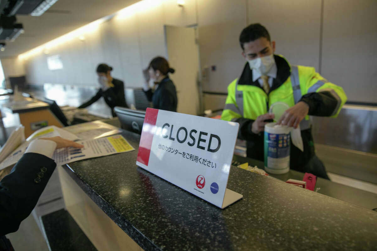 SEATTLE, WA - MARCH 15: A ground crew cleans behind a counter at check-in at the Seattle-Tacoma International Airport on March 15, 2020 in Seattle, Washington. The state of Washington has over 600 confirmed cases of coronavirus (COVID-19) and U.S. airports have been crushed with returning citizens after restrictions on travel from Europe were implemented. (Photo by John Moore/Getty Images)