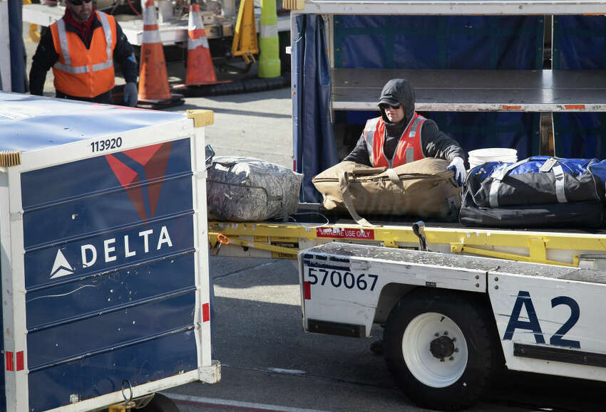 SEATTLE, WA - MARCH 15: A ground crew unloads luggage from an arriving Delta Airlines flight at the Seattle-Tacoma International Airport on March 15, 2020 in Seattle, Washington. (Photo by John Moore/Getty Images)