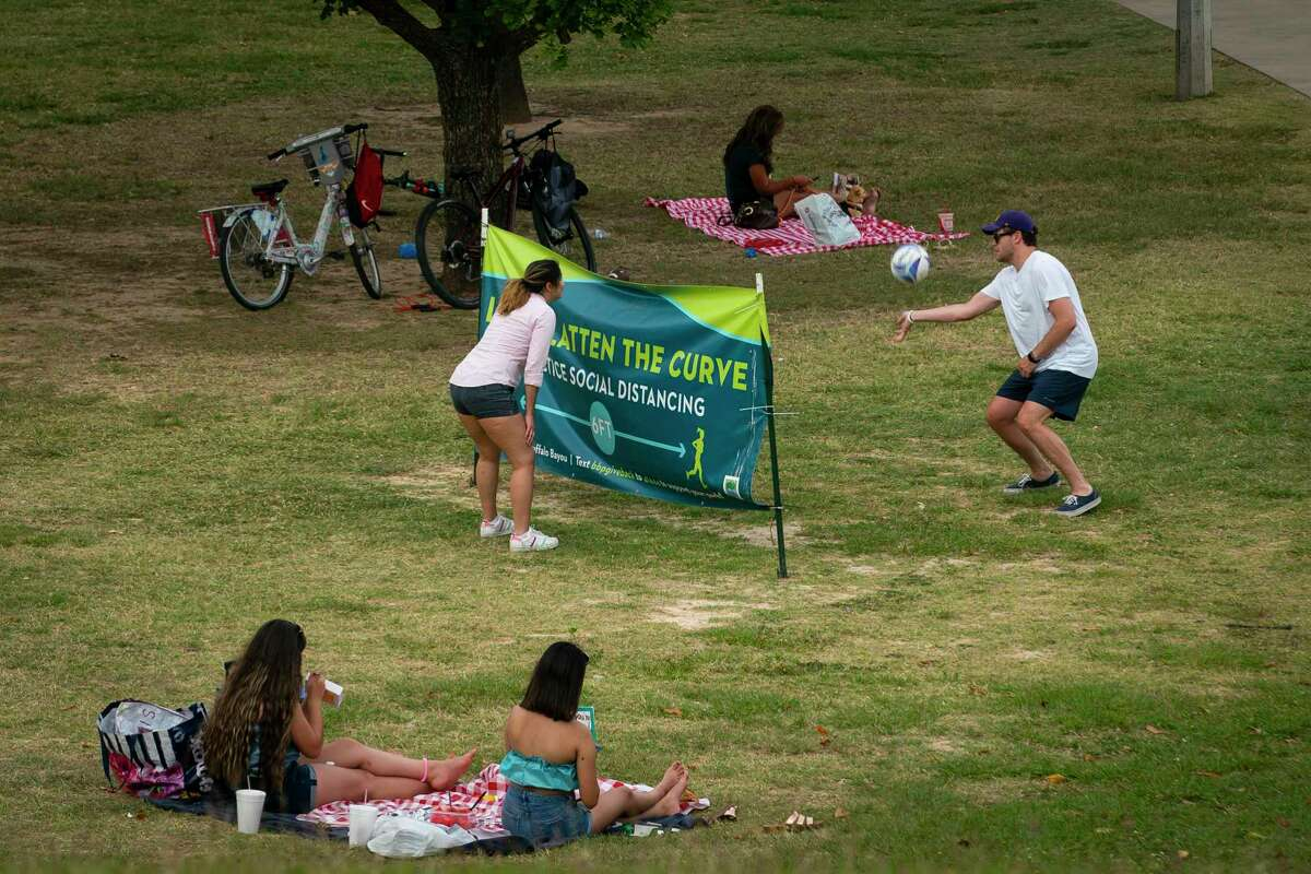 People use a sign urging people to practice social distancing as a net to play volleyball along Buffalo Bayou near Eleanor Tinsley Park in Houston.