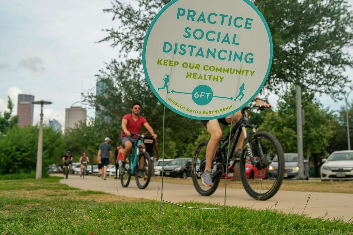A sign urges people to practice social distancing while enjoying mild weather along Buffalo Bayou near Eleanor Tinsley Park in Houston.