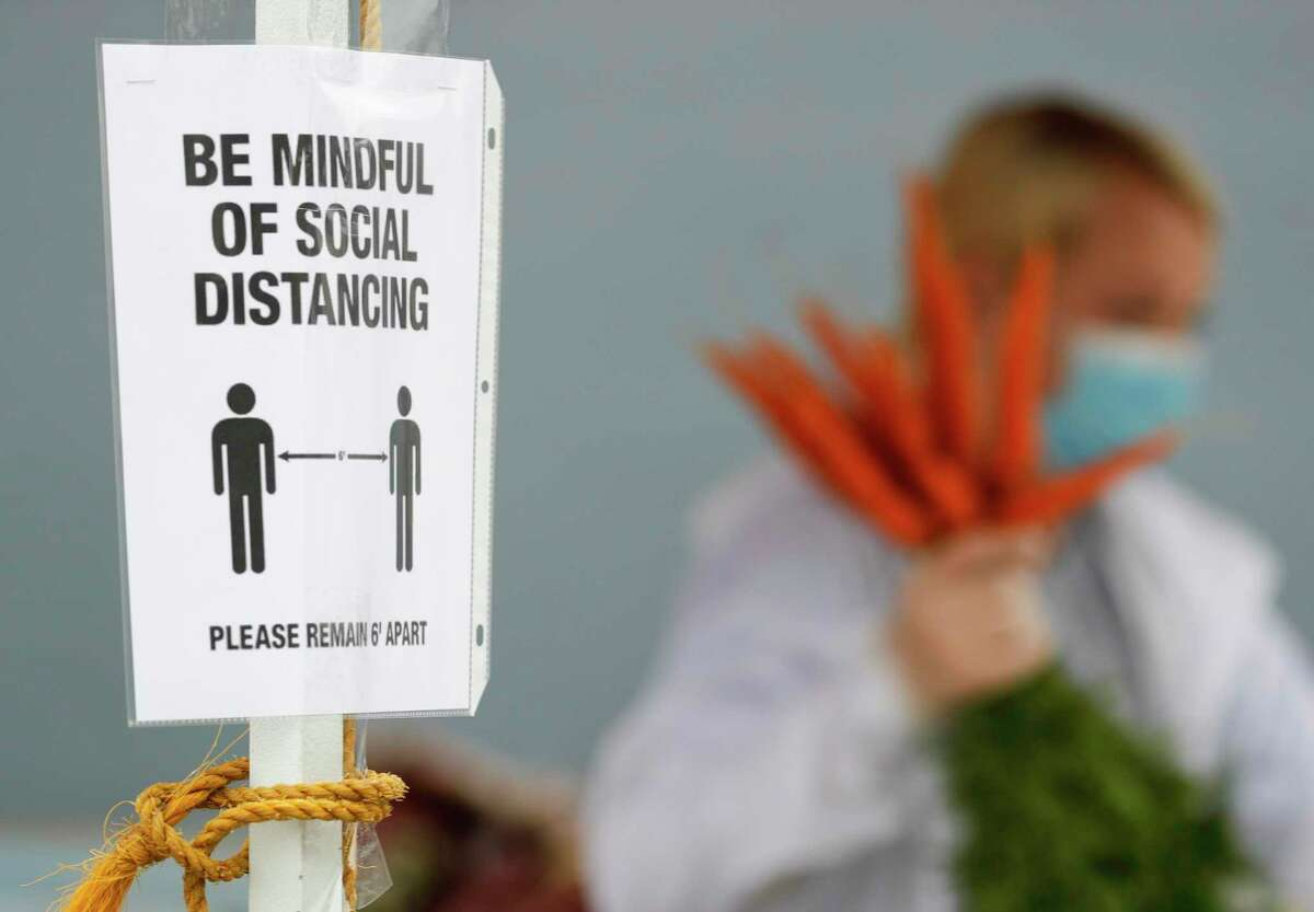 A sign reminds visitors to use social distancing at the Tomball Farmers Market.