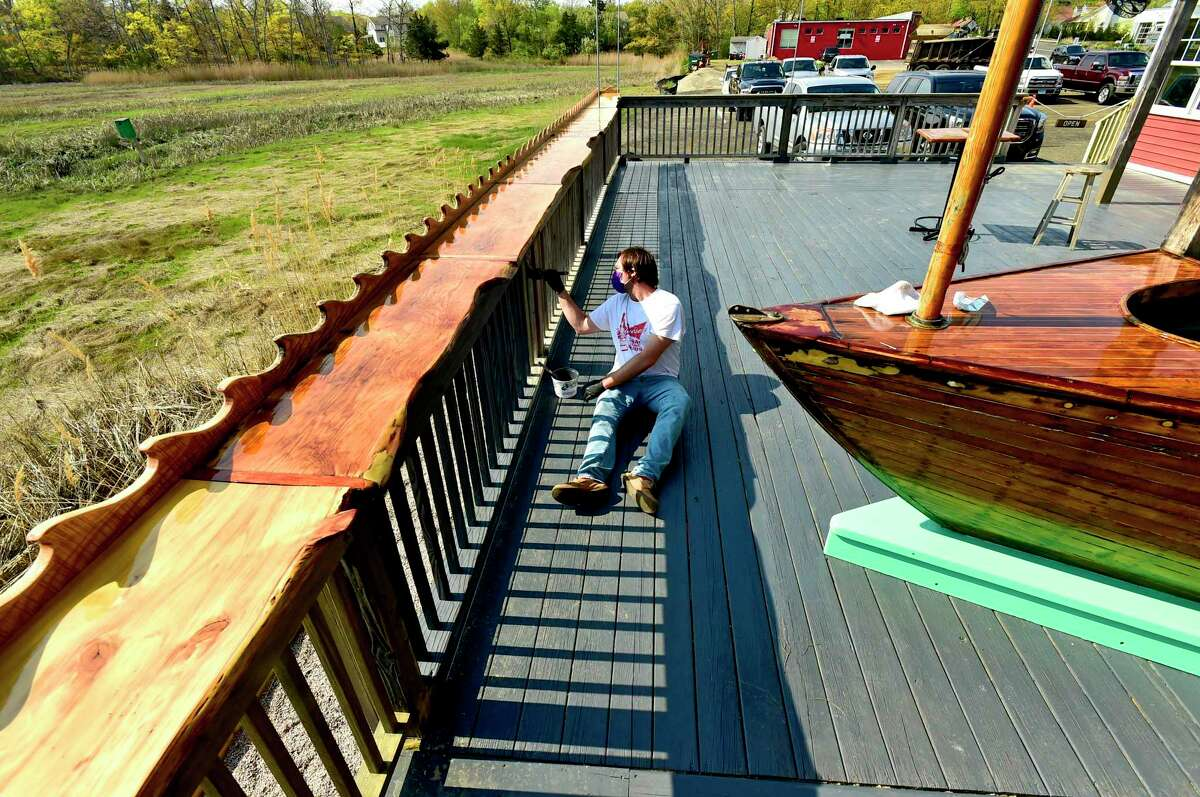 Branford, Connecticut - Friday, May 15, 2020: Brendan Conlin, son of owner Christopher Conlin of Lenny's Indian Head Inn, paints the back deck next to Sybil Marsh at the classic New England seafood restaurant. The Conlin's and the staff will be getting ables ready on their back deck and patio area, and in their parking lot as Connecticut restaurants prepare for a staged May 20th opening due to the Coronavirus / Covid-19 pandemic.