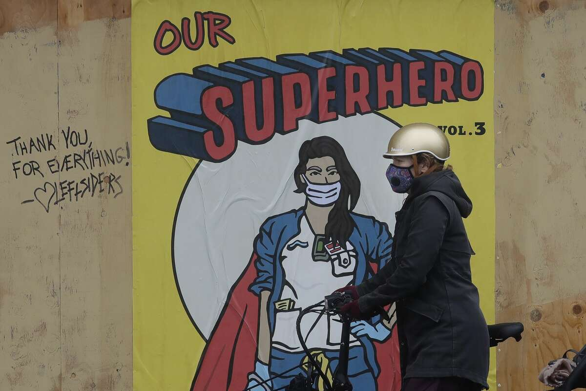 A woman wears a face mask in front of a poster of a masked superhero outside of a boarded up Optometrix eye care center during the coronavirus outbreak in San Francisco, Thursday, May 14, 2020.