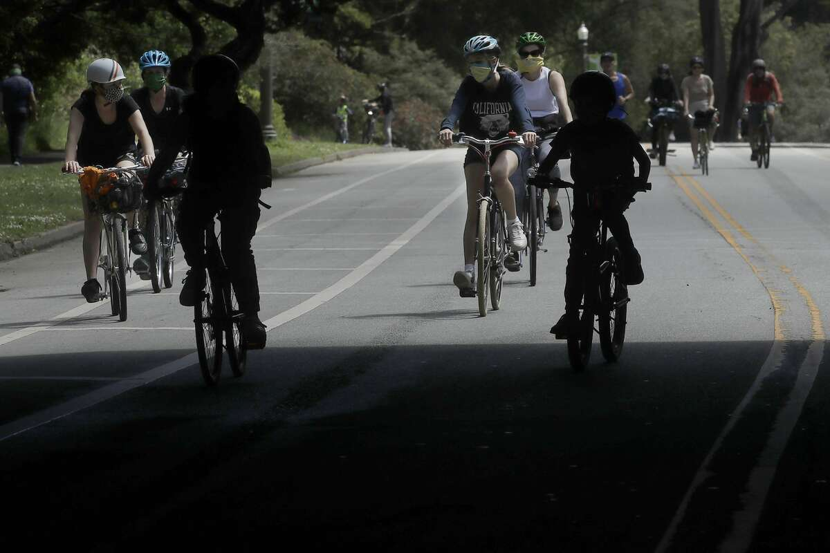 People wear face masks while bicycling on a closed street next at Golden Gate Park during the coronavirus outbreak in San Francisco, Sunday, May 17, 2020.