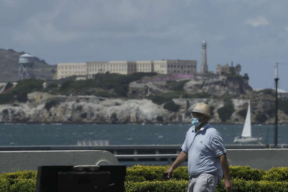 A man covers his face with a mask while walking on a path at Aquatic Park in front of Alcatraz Island during the coronavirus outbreak in San Francisco, Sunday, May 17, 2020.