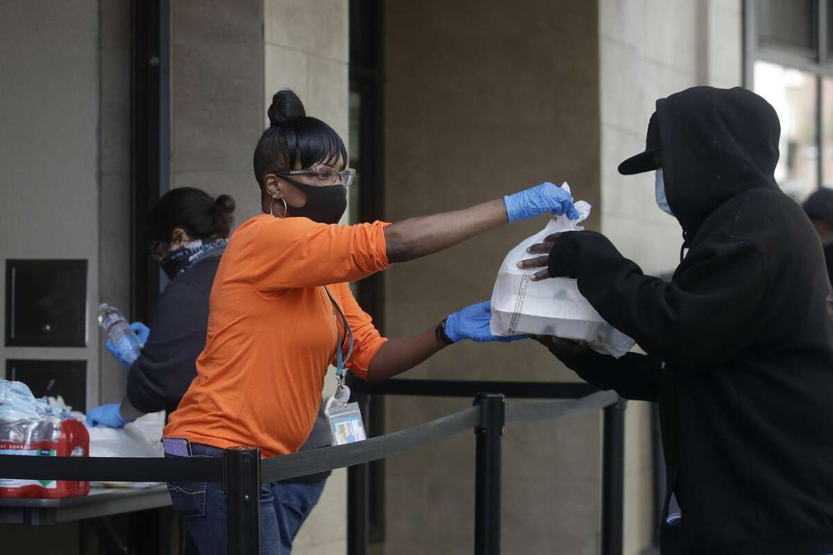 Felicia Senigar, left, an employee of St. Anthony's, wears a mask as she hands out food in San Francisco, Thursday, April 30, 2020. Senigar, the charity's housing clinic manager, said she cried along with residents as they got socks, hygiene kits, a $50 Walgreens gift card and a bag of groceries from St. Anthony's.