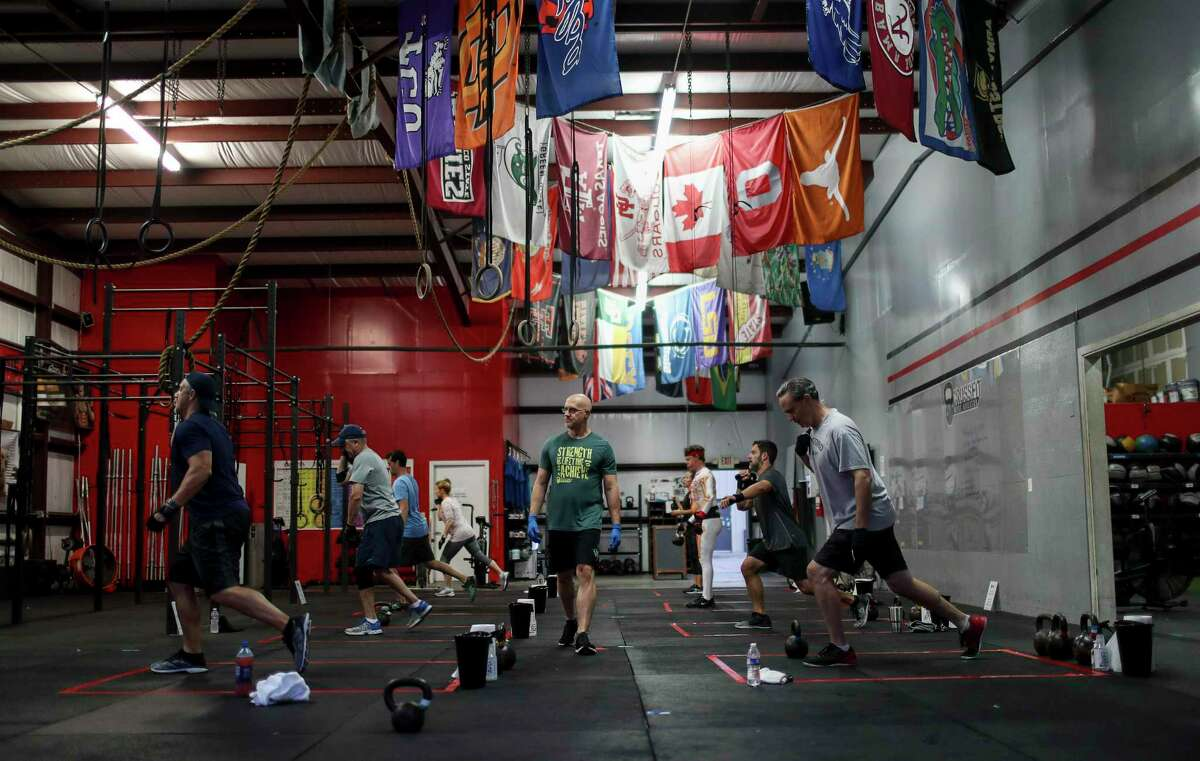Rob Exline, center, owner of Crossfit West Houston, leads an early-morning class Monday, May 18, 2020, at his gym in Houston.