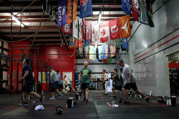 "Rob Exline, center, owner of Crossfit West Houston, leads an early-morning class Monday, May 18, 2020, at his gym in Houston. ""It's good to kind of knock the rust off,"" he said. ""It'll be nice to get back to the whole routine."" Governor Greg Abbott allowed gyms and some other businesses to reopen today at reduced capacity, as part of his phased reopening plan for the state."