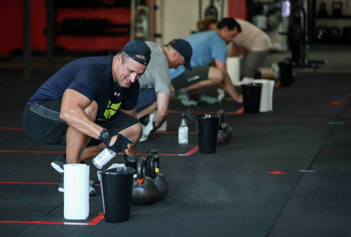 Jesus Iglesias cleans a set of kettlebells after a crossfit class Monday, May 18, 2020, at Crossfit West Houston in Houston. Governor Greg Abbott allowed gyms and some other businesses to reopen today at reduced capacity, as part of his phased reopening plan for the state.