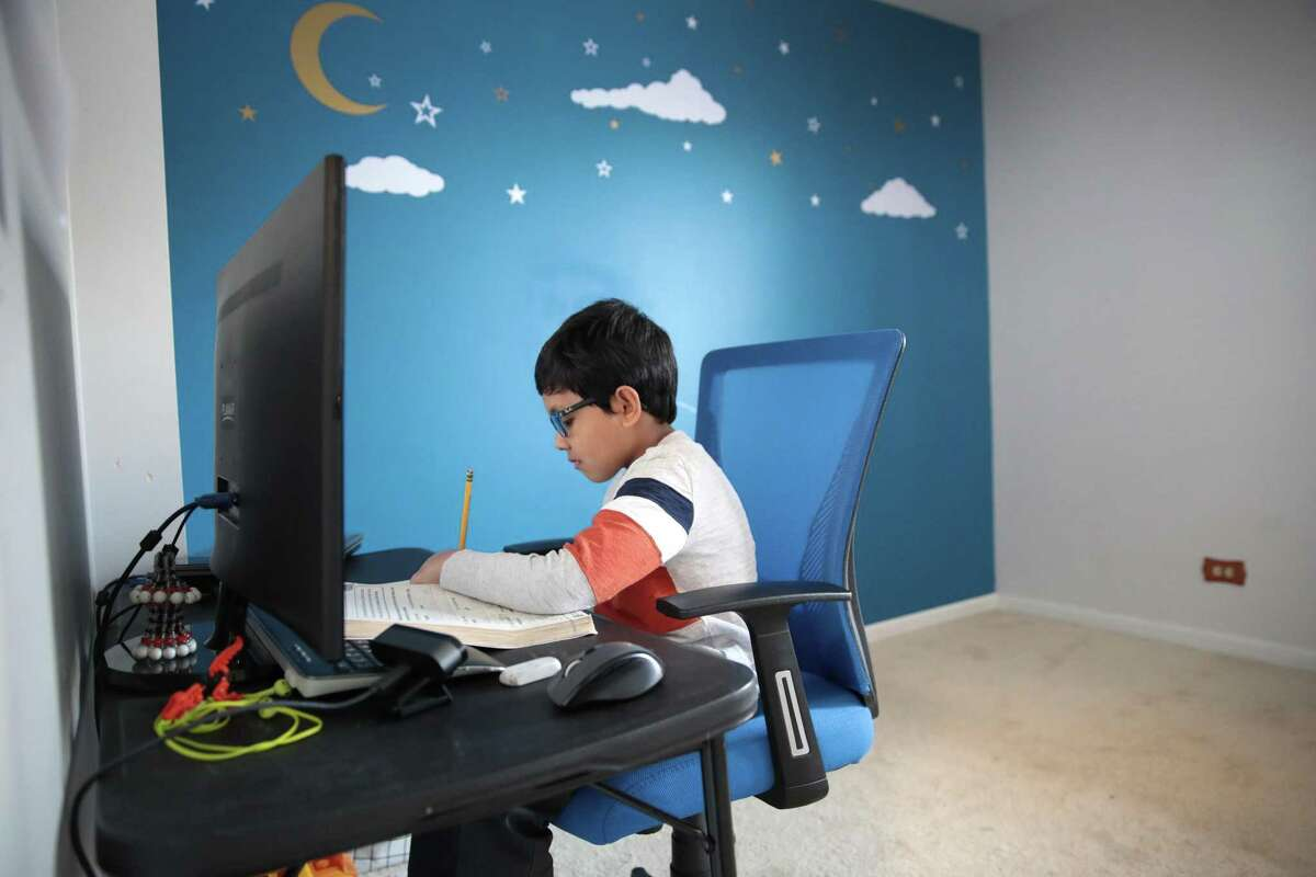 A 7-year-old second-grade student uses a computer to participate in an e-learning class with his teacher and classmates while at his home May 1.