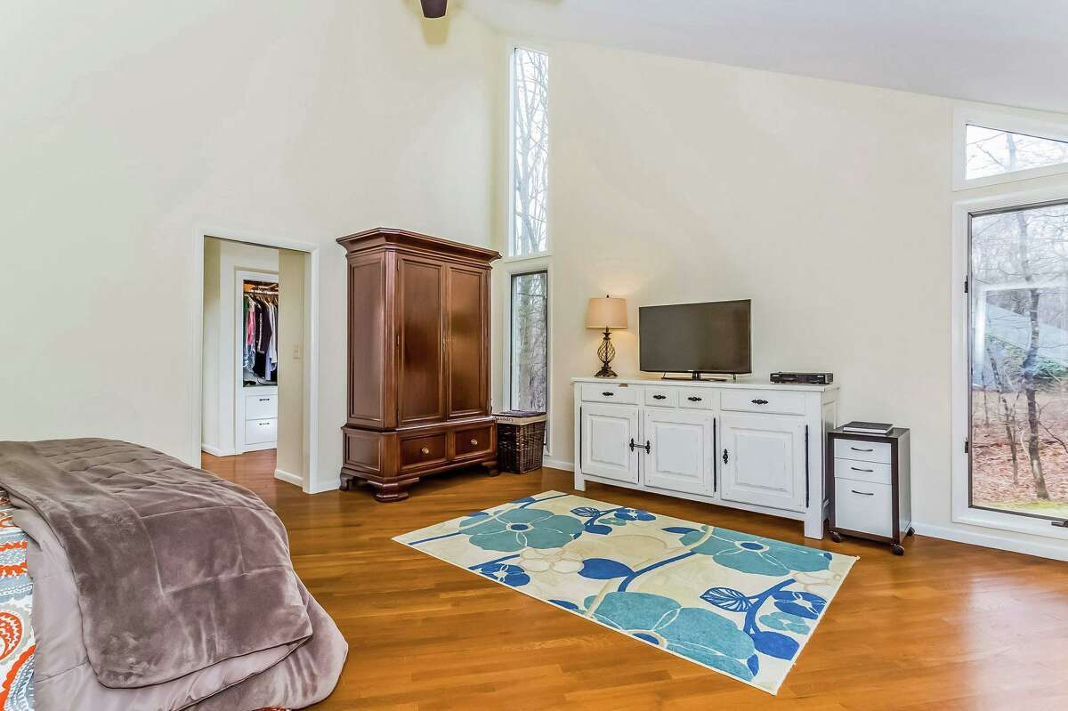 The first floor master bedroom suite features a tall vaulted ceiling, ceiling fan, walk-in closet, private bath, and sliding doors to a private balcony.