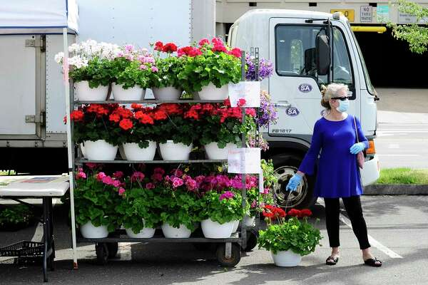 A patron waits with her purchases while shopping at the Greenwich Farmers Market in Greenwich, Connecticut on May 16, 2020.