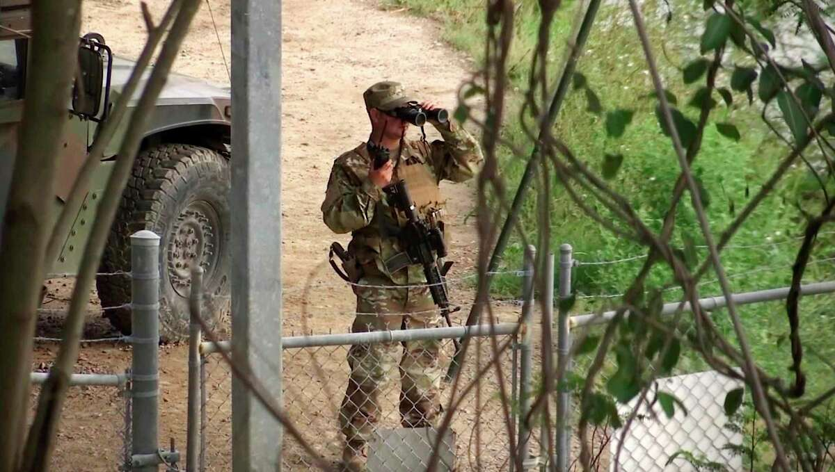 FILE - In this April 10, 2018, file frame from video, a National Guard troop watches over Rio Grande River on the border in Roma, Texas. (AP Photo/John Mone, File)