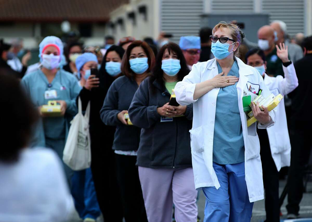 Nurses are applauded by police and firefighters as they leave Kaiser Hospital at the end of their shift on May 14, 2020 in South San Francisco, California. Police and firefighters from South San Francisco, Colma, Daly City, Brisbane and Pacifica lined up outside of Kaiser Hospital to thank health care workers who are working on the front lines of the coronavirus COVID-19 pandemic.