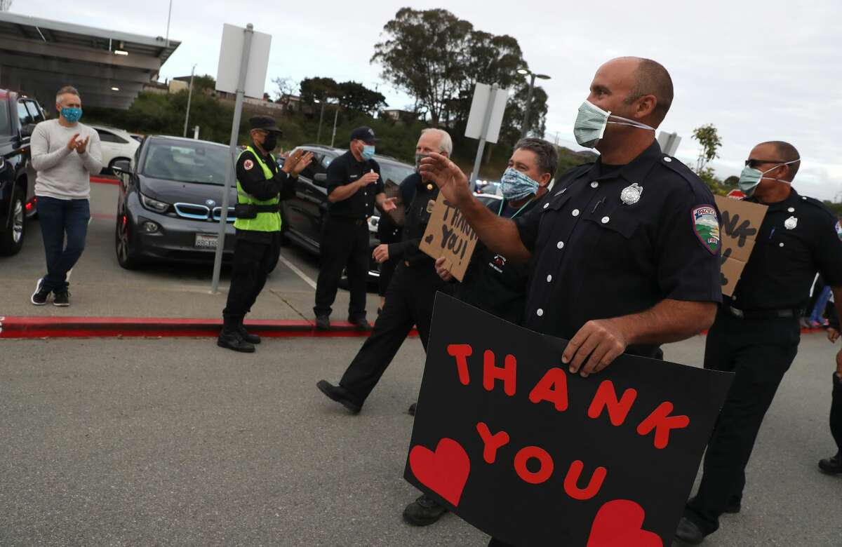 South San Francisco firefighters hold thank you signs as they honor front line workers at Kaiser Hospital on May 14, 2020 in South San Francisco, California. Police and firefighters from South San Francisco, Colma, Daly City, Brisbane and Pacifica lined up outside of Kaiser Hospital to thank health care workers who are working on the front lines of the coronavirus COVID-19 pandemic.