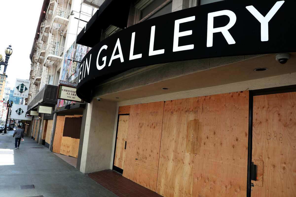 A pedestrian walks by boarded up businesses on May 15, 2020 in San Francisco, California. Malls and other businesses shutdown in an attempt to contain the coronavirus causing the U.S. retail sales to fall by a record 16.4% from March to April.