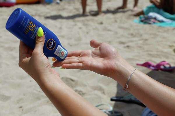 A young woman is using sunscreen on Muro's beach.