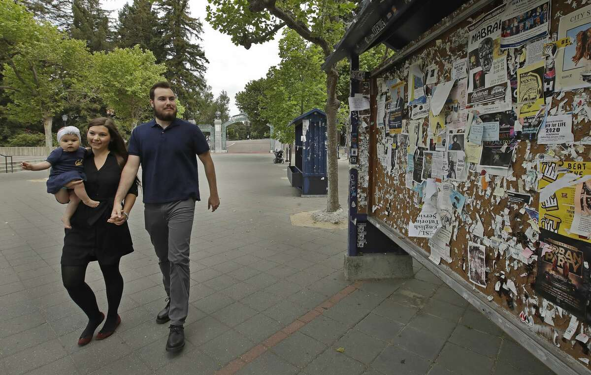 FILE: University of California at Berkeley graduate Tyler Lyson walks with his wife, Lucie, who is holding their 8-month-old daughter, Lisa, as they walk past a student activity billboard on the closed Cal campus in Berkeley, Calif., on Monday, May 11, 2020.
