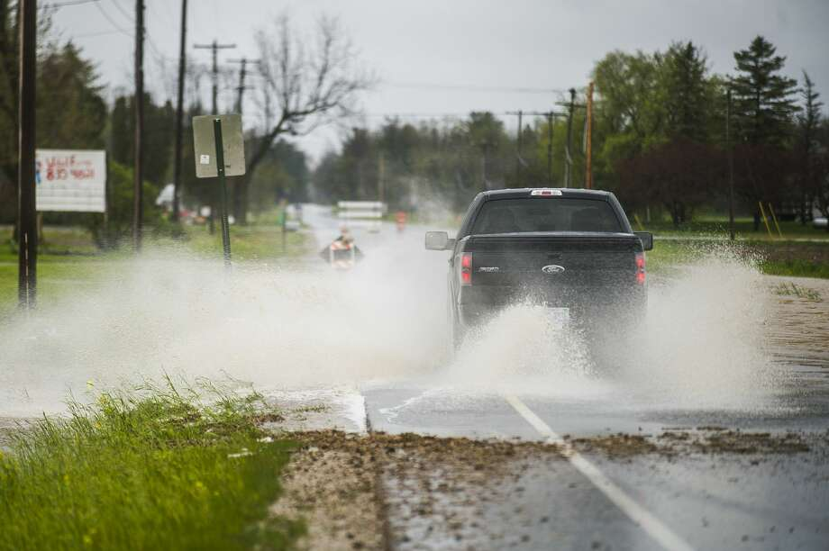 A vehicle drives through a large puddle of water on Eastman Road, between Hubbard and Bombay, Monday morning, May 18, 2020 in Midland. (Katy Kildee/kkildee@mdn.net) Photo: (Katy Kildee/kkildee@mdn.net)