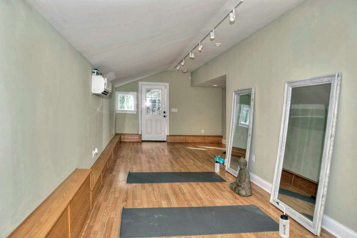 A space attached to the detached three-car garage could serve as an office, or as an art, exercise, yoga, or recording studio.