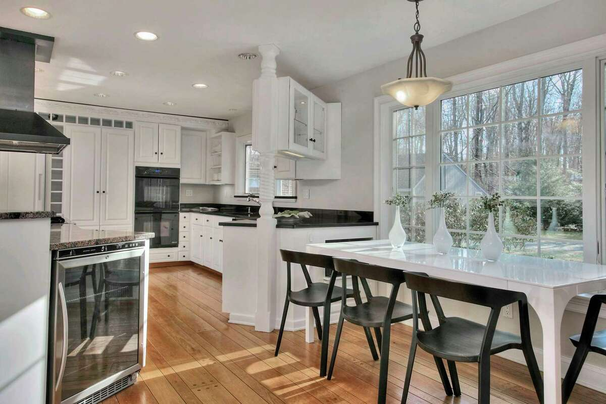 The eat-in kitchen has granite counters, random-width pegged flooring, and a large casual eating area or breakfast room.
