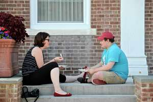 """Dana Fotheringham, left, and Thomas Smith, both from Bethel, sit on the front steps of the Bethel Municipal Center and enjoy a BBQ dinner during Food truck Friday. The event included food, games and music on the lawn of the municipal center on Friday evening, August 5, 2016, in Bethel, Conn. The next """"Food truck Friday"""" will be Friday evening, August 19th."""