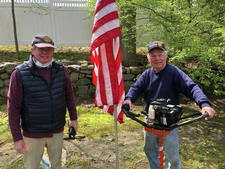 Jim Finklea and Mike Anderson help install an American flag in town. Photo: Contributed Photo