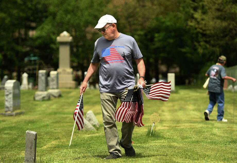 Donald Tagg, of Shelton, and fellow members of American Legion Post 16 place flags at the graves of military veterans at Lawn Cemetary on Sunday. Photo: Brian A. Pounds / Hearst Connecticut Media / Connecticut Post